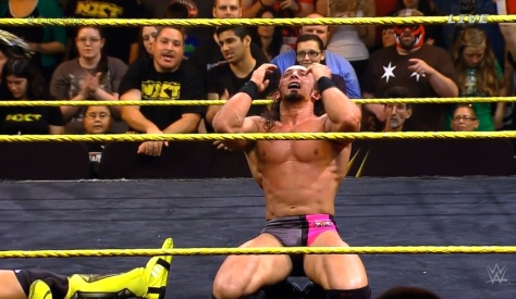 Adrian Neville celebrates after retaining the NXT Championship.